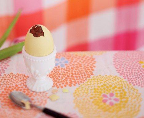 Vanligt äggskal fyllt med choklad istället för vita och gula, i vit skir porslinskopp på färgglad duk.