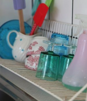 Diskställ med pasellfärgade glas och koppar, intill står en sprayflaska med diskmedel.