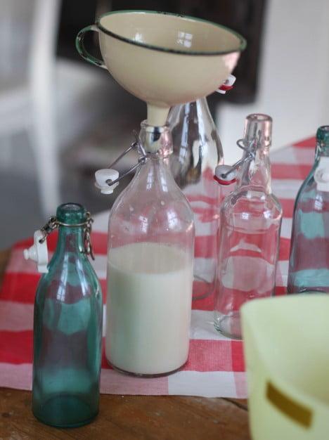 Här har jag hällt färdig havremjölk ner i glasflaskan med hjälp av en fin emaljtratt.