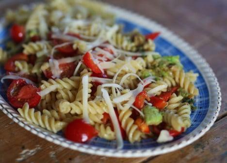 Varm pasta med tomat och avokado på köksbordet.