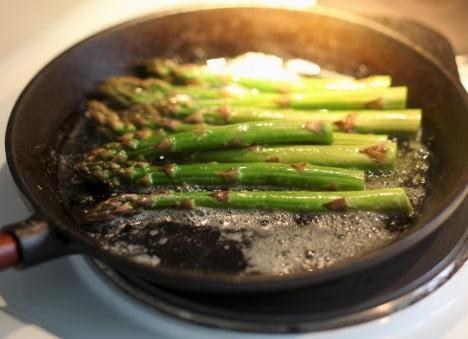 Grön sparris steks i smör i stekpannan.
