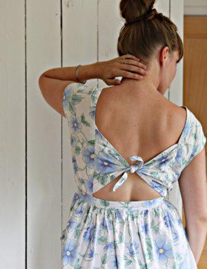 Clara i en klänning där bakstycket knyts i ryggen och lämnar en liten glipa kvar där ryggen skymtar fram