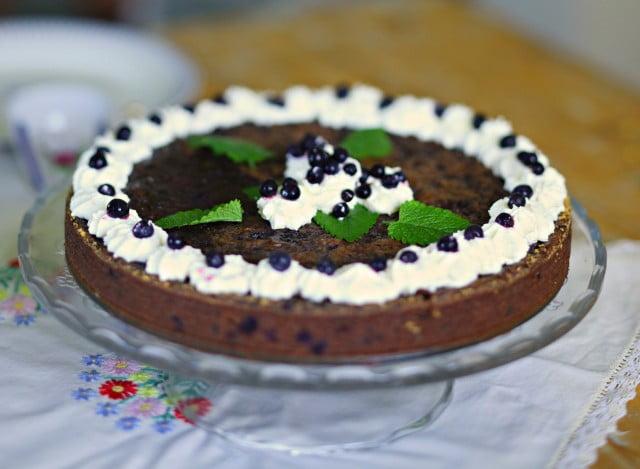 Rund blåbärsspäckad kladdkaka på tårtfat med fot. Kakan är dekorerad med grädde och bär.