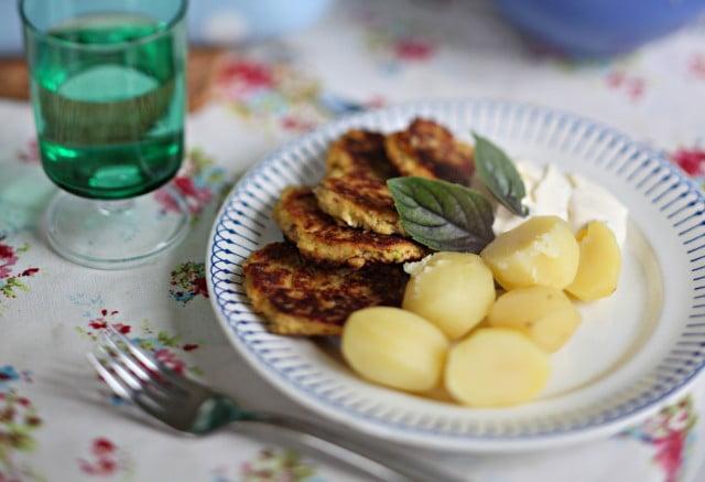 Fyra grönsaksbiffar serverade med kokt potatis.
