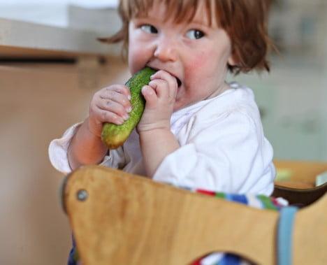Liten gurkslukare i barnstol.