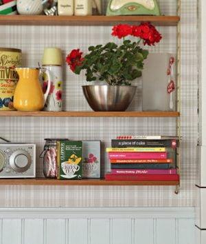 Kökshylla med radio, röd pelargon, kokböcker och porslin i glada färger.