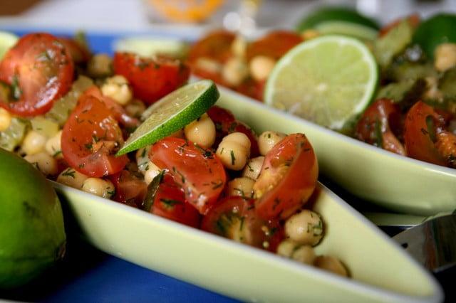 Sallad med tomat, kikärtor och saltgurka serverad i smalt avlångt uppläggningsfat.