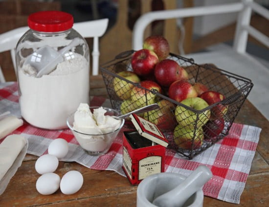 Äpplen och bakingredienser på köksbordet.
