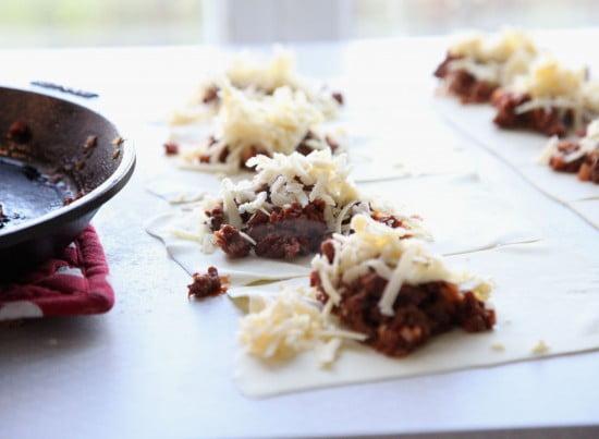 Smördegsrutor med små fyllningar av älgfärs och ost redo att vikas ihop.