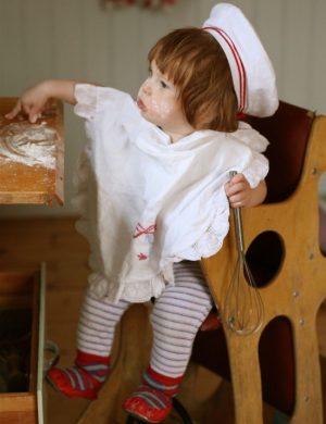 Sonen Bertil sitter i barnstol vid bakbord, klädd i förklä och vit mössa, kladdar med lilla barnhanden i deg.