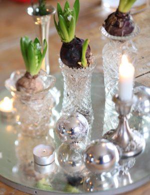 gammal rund spegel som ligger ner dekorerad med ljus, vaser och runda silverkulor.