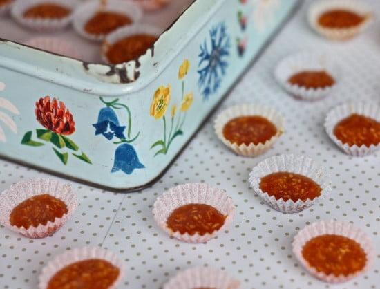 Knäckformar fyllda med saffransknäck på prickig duk med blommig plåtburk i brakgrunden.