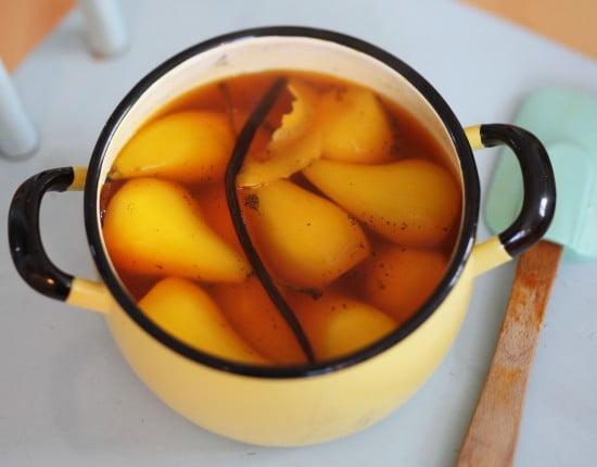 Saffransgula päron i kastrull med vaniljstång.