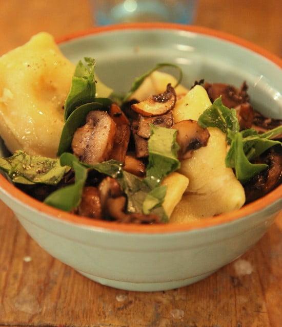 Nykokt ravioli med skurna skivor av svamp och sallad till.