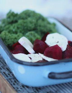 Blå ugnsform i emalj med grönkål, rödbeta och ost i skivor.