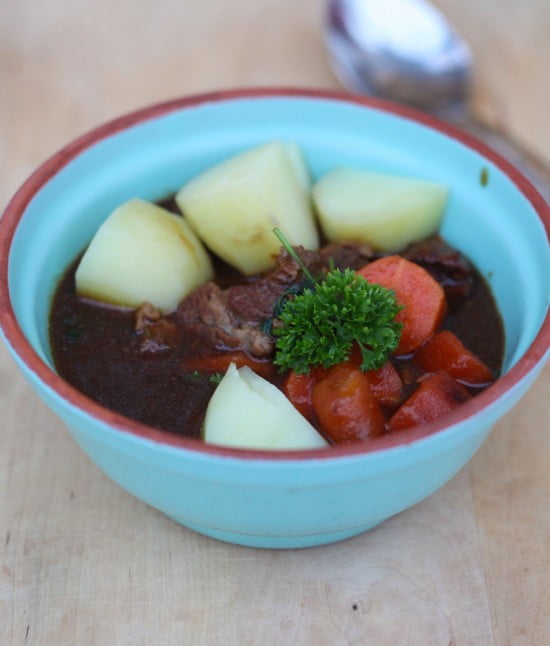 Mörk kalops i sky med bitar av morot och potatis i pastellblå skål.