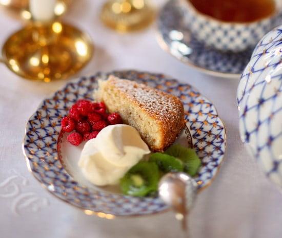 Mandelkaka med florsocker serverad med gräddklick och hallon med kiwiskivor på blåmönstat porslin med gulddetaljer.