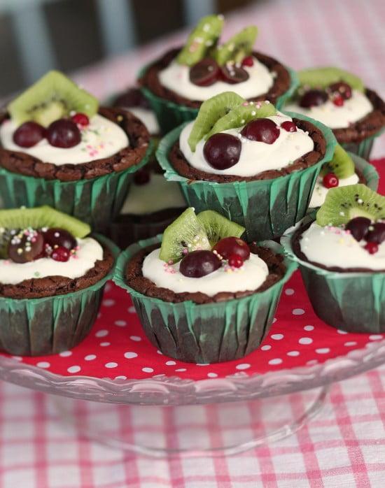 Muffins av kladdkaks-smet står färdigbakade på tårtfat. De är dekorerade med grädde och frukt.
