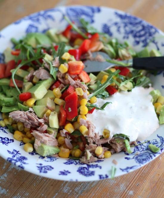 Lunchtallrik med skuren avokado, sallad, majs, paprika och tonfisk.
