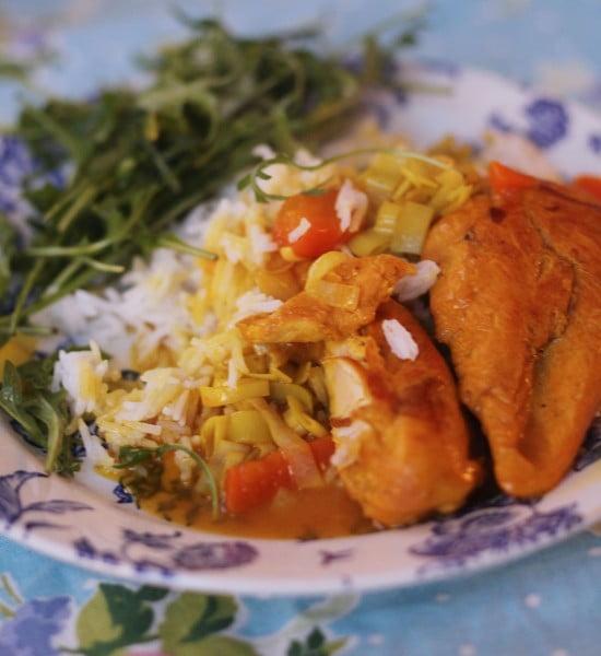 Gyllenbrun kyckling serverad med ris och purjo.