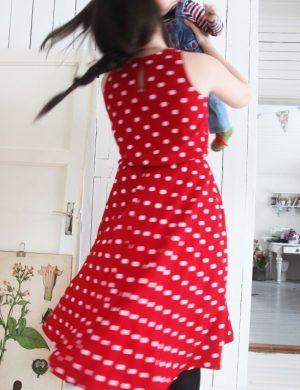 Clara i röd lång klänning snurrar runt med Bertil som baby i sina armar, de snurrar så fort att klänningens tyg och fläta står rakt ut.