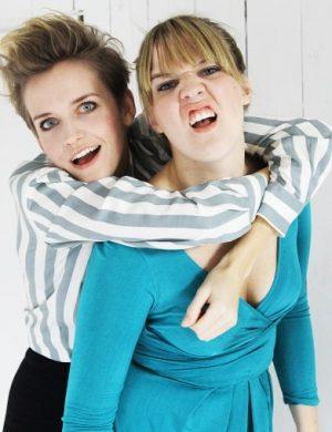Clara grimaserar mot kameran med gristryneaktig min och sin syster Anna som hänger på ryggen.
