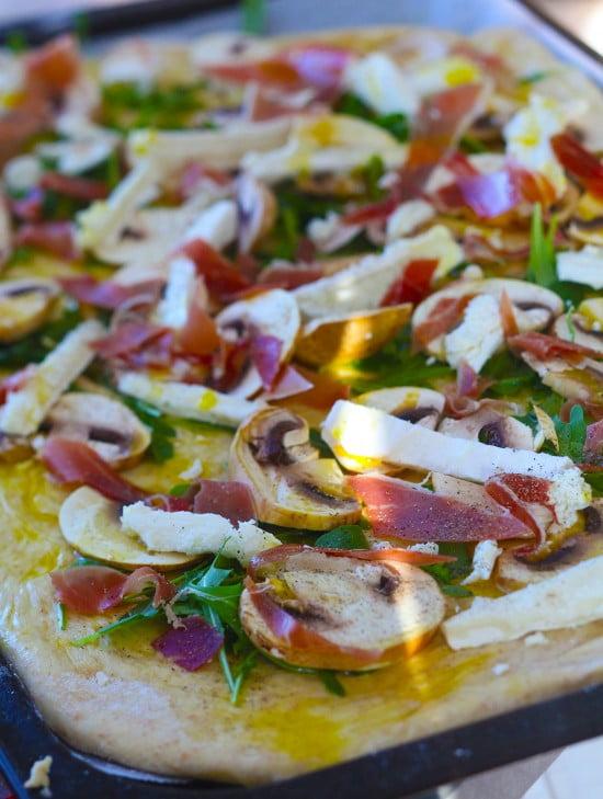 Färska skivade champinjoner, chevre och lufttorkad skinka på pizzabotten.