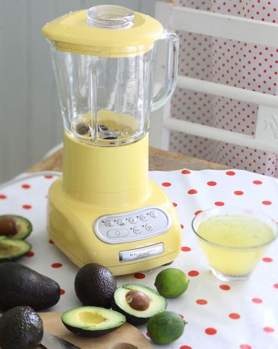 Delande avocadofrukter med min gula mixer på köksbordet.