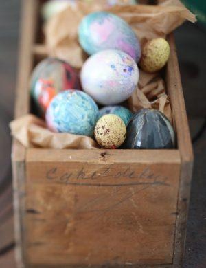 Vackert färgade ägg i olika blå och lila toner, ligger i gammaldags trälåda.