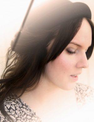 Dimmig bild i motljus på Clara i mörkt långt hår och liten svart hatt på huvudet.