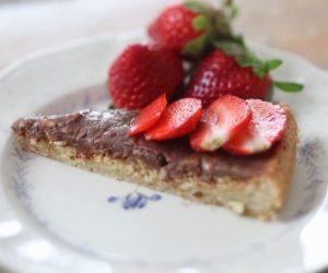 Låg nötig kaka på fat toppad med skivade jordgubbar.