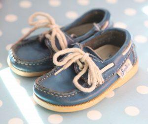 Små blå barnskon i seglarstil med vita snören.