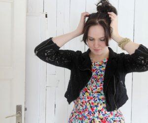 Clara klädd i svart jacka och blommig klänning, håller upp håret i en knut på huvudet.