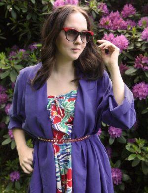 Clara i blå kappa och solglasögon framför somriga lila buskar.