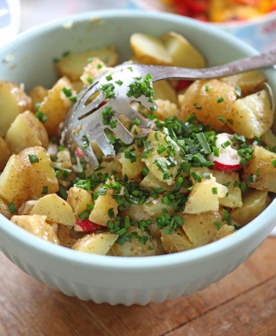 Skuren potatis med rädisor i skivor och hackad gräslök blandade i en vit skål.