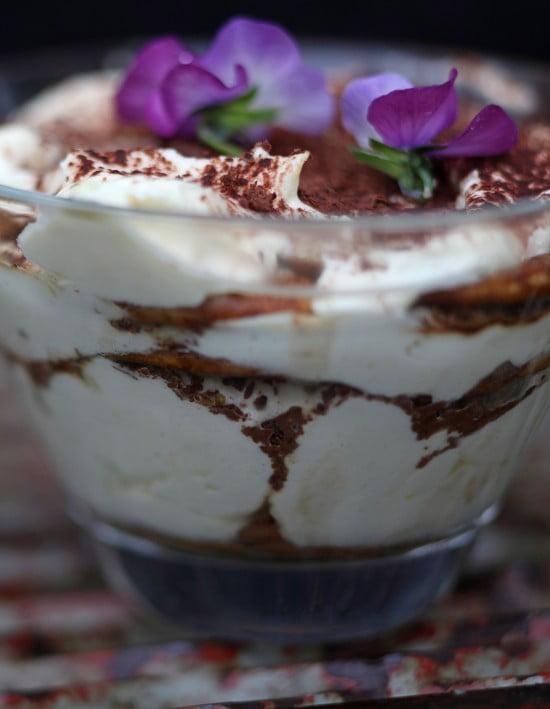 En tiramisu i närbild med lager av vitt som varvas med brun kakao.