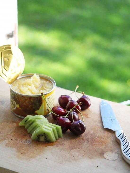 Krossad annanas på burk, skivad kiwi och djupröda körsbär.