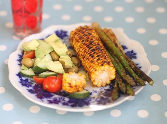 Sommarlunchen med sparris och färdiggrillad majskolv på tallrik med sallad av gruka, tomat och gröna oliver.