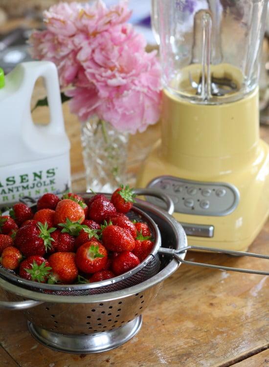 Durkslag i metall fullt med jordgubbar.