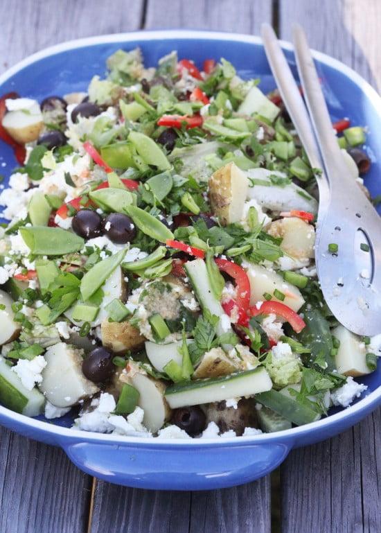 Stor sommarsallad i blå skål med grönsaker, oliver, fetaost och färska kryddor.