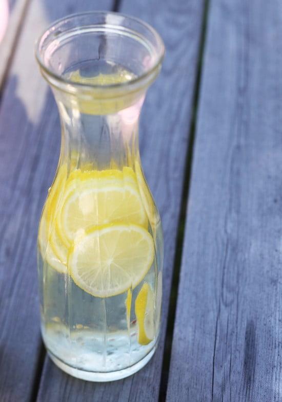 Glaskaraff med skivade citroner i vatten.