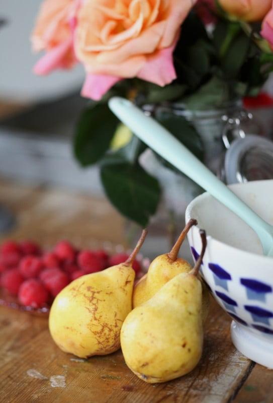 Bleka söta päron och färska hallon under rosbukett på träbord.