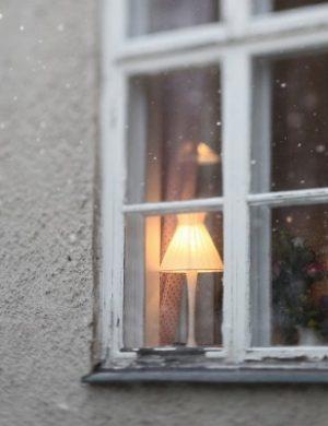 Claras vita puts hus fotat utifrån i lätt snöfall, närbild på fönster med tänd lampa