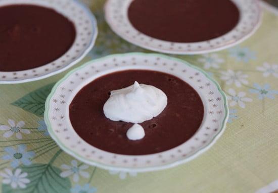 Chokladpudding serverad i ljusa desserttallrikar med en klick grädde.