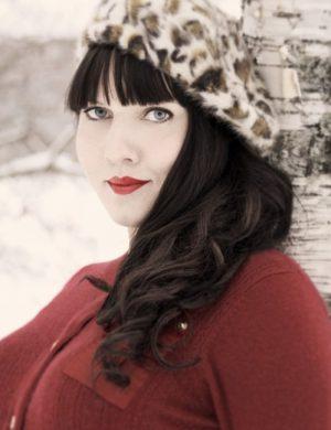 Clara utomhus i kallt väder, klädd i djurmönstrad mössa och vinröd kofta.