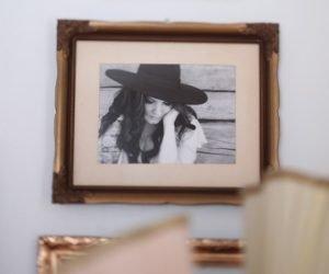Bild på tavla som hänger på väggen, motivet är Clara i svartvitt med hatt. Foto inramat i guldram.