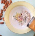 Fat med hyvlade mandelspån som står på ljus köksduk.