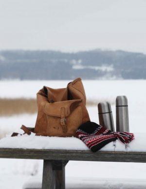 Vy med fjäll i bakgrunden, framför står en bänk med utflyktsryggsäck och uppackade termosar.
