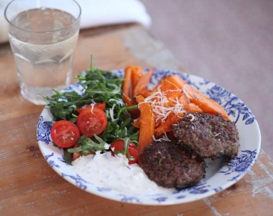 Runda små biffar serverade med grönsaker som morot och körbärstomater skurna i halvor på blåvitt porslin.