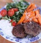 Uppdukad tallrik med två köttbiffar och färgglada grönsaker som morot, tomat och sallad.